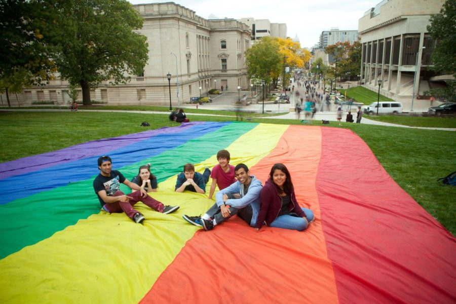 A group of students sitting on a giant rainbow flag