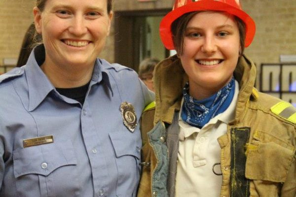 A QUELP alum wearing a firefighter hat with a firefighter