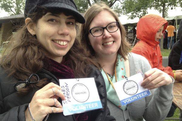 Two women smiling and holding Disability Pride Madison volunteer badges
