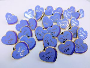 "Pile of purple heart enamel pins reading ""Is this OK"" on each"